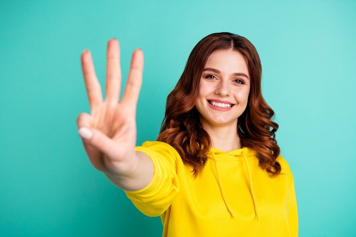 Lady holding out 3 fingers
